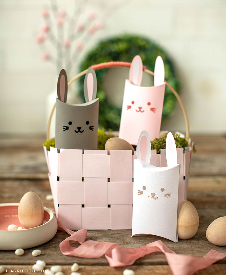 papercut bunny pillow box in grey, pink, and white with pink Easter basket and wooden eggs in front of paper wreath and blooming branch