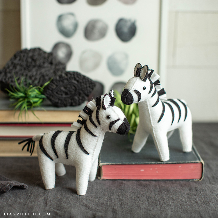 felt zebra stuffie friends near books and wall art