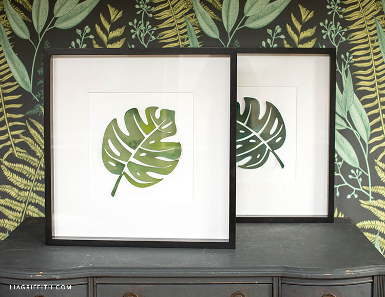 painted monstera leaf artwork on dresser with leaf printed wallpaper in background