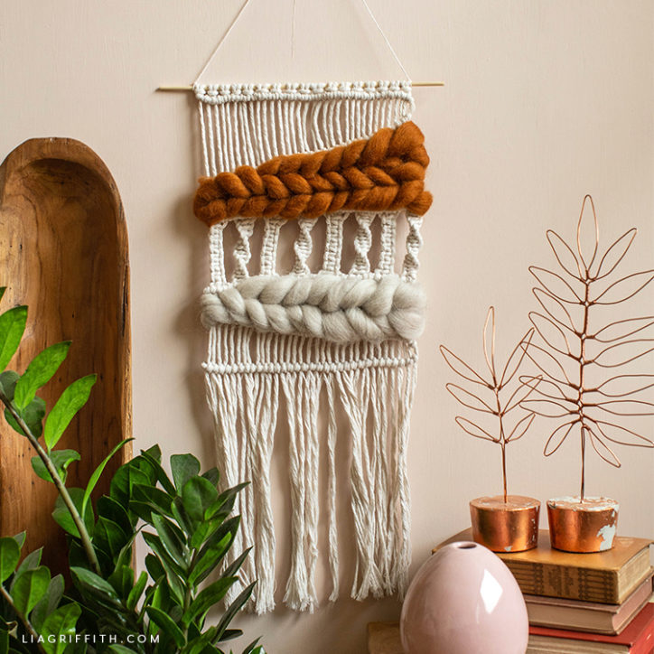 macramé and woven wool wall hanging next to wooden tray, copper wire leaf décor, pink vase, and plant