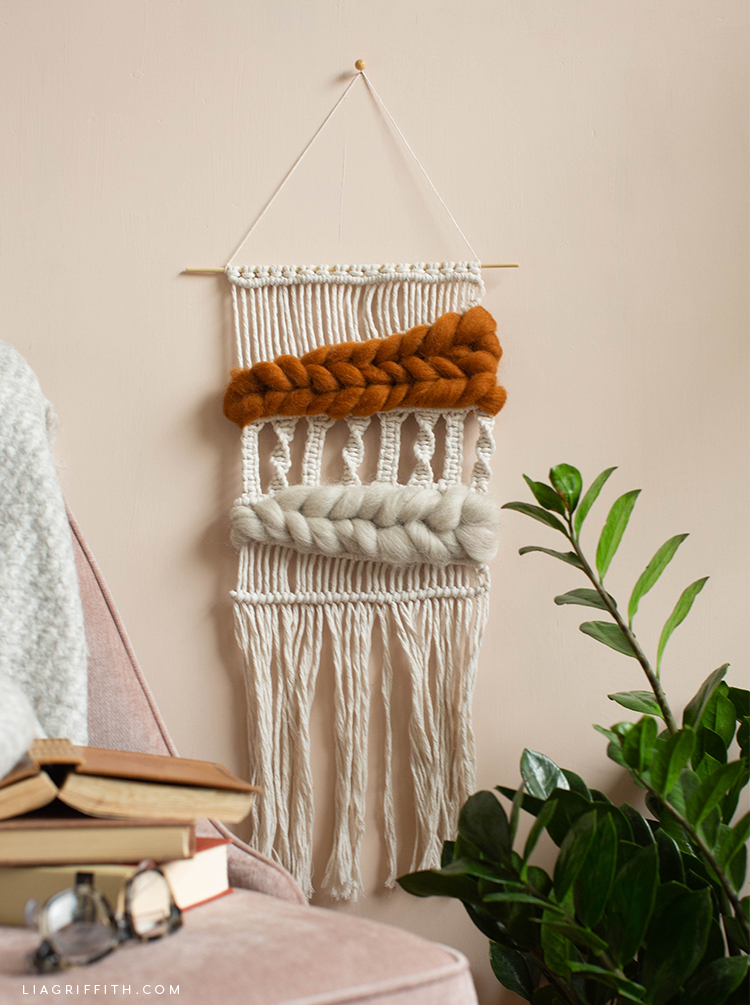 macramé and woven wool wall hanging next to plant