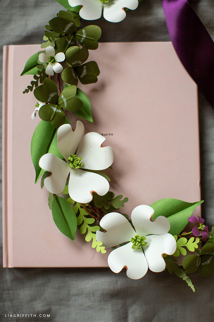 part of paper shamrock and dogwood wreath on pink book