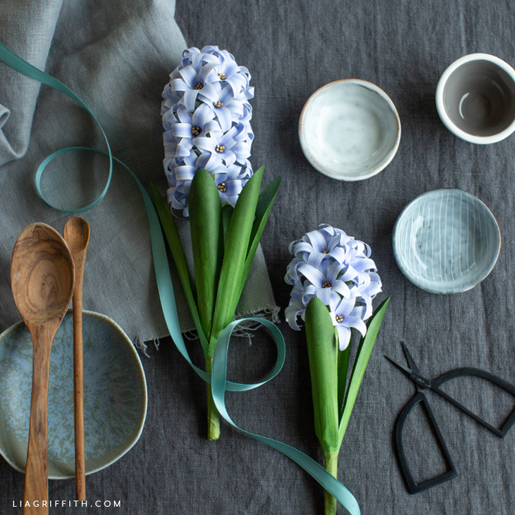 frosted paper hyacinth flowers next to little bowls, wooden spoons, scissors, and ribbon