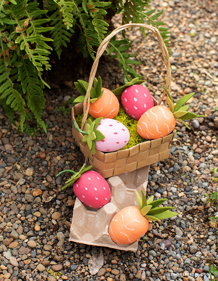 carrot and strawberry Easter eggs in basket and egg carton outside on rocks