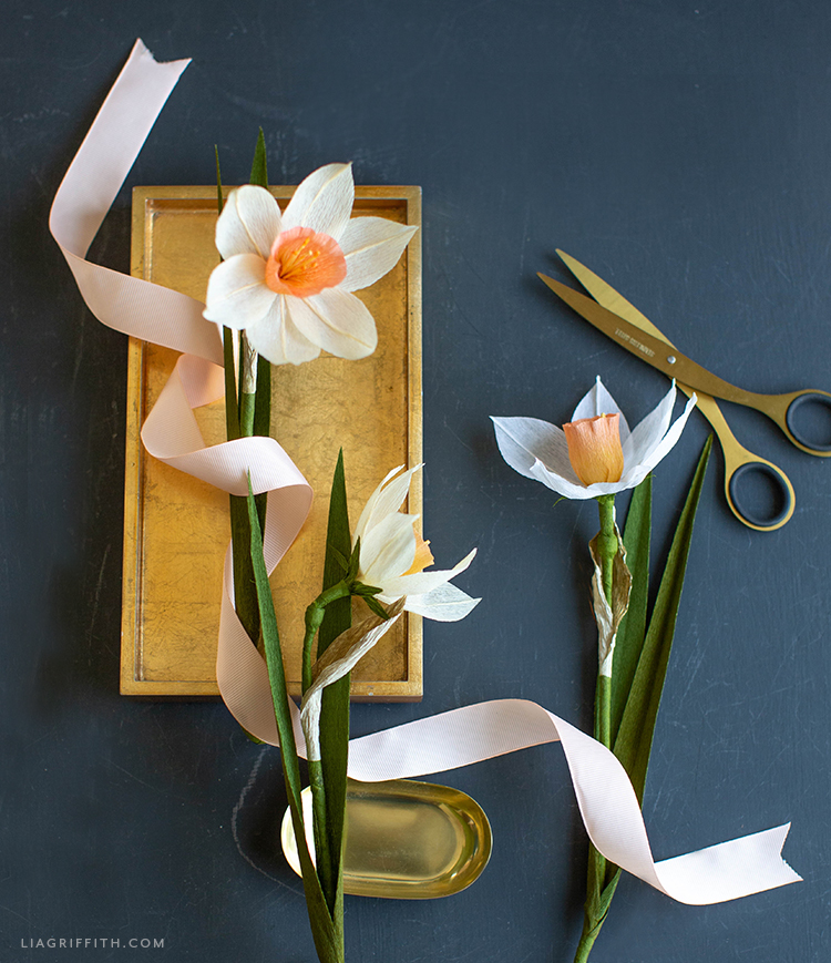 crepe paper daffodils on gold tray with pink ribbon and gold scissors