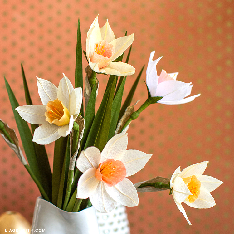 crepe paper daffodils in white vase with orange background