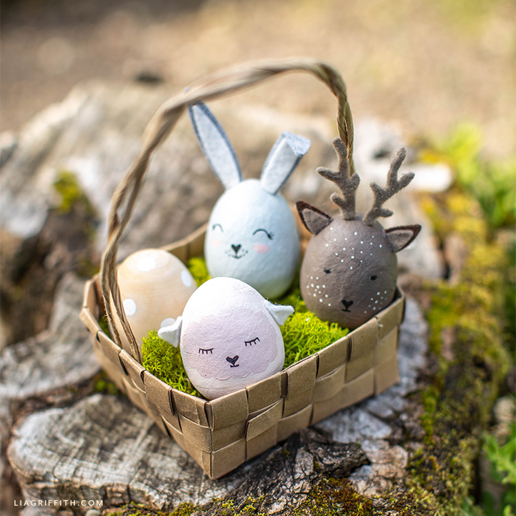 painted animal Easter eggs in Easter basket on top of tree stump outside
