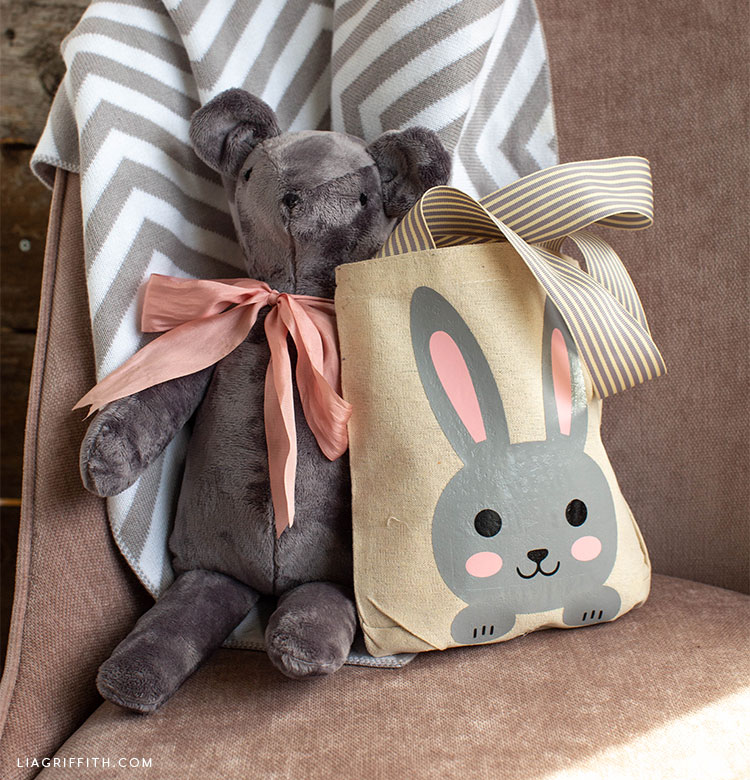 Easter tote bag with bunny iron-on next to stuffed bear and blanket