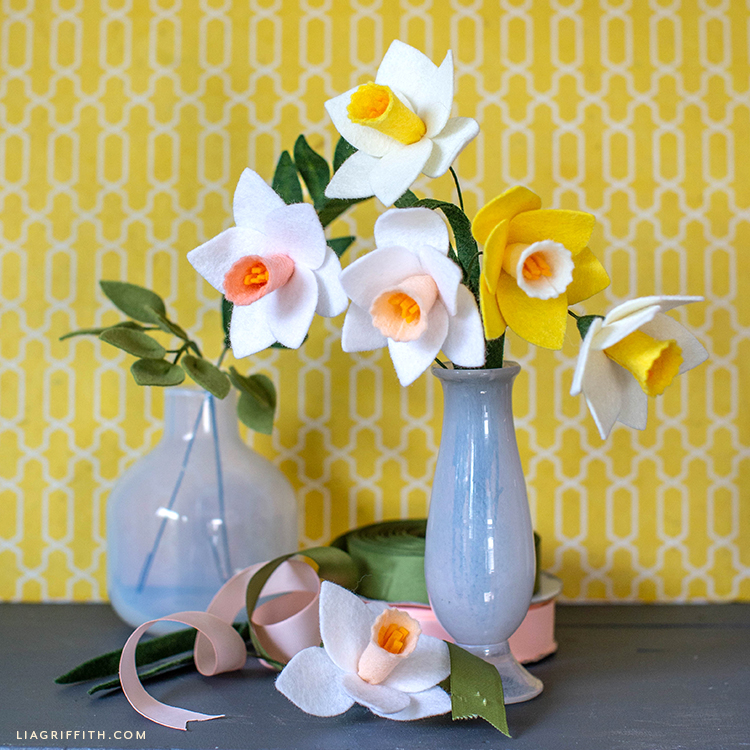 felt daffodils in grey vase in front of yellow and white wall