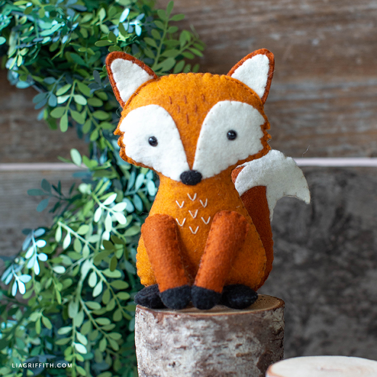 felt red fox stuffie sitting on little stump in front of paper wreath