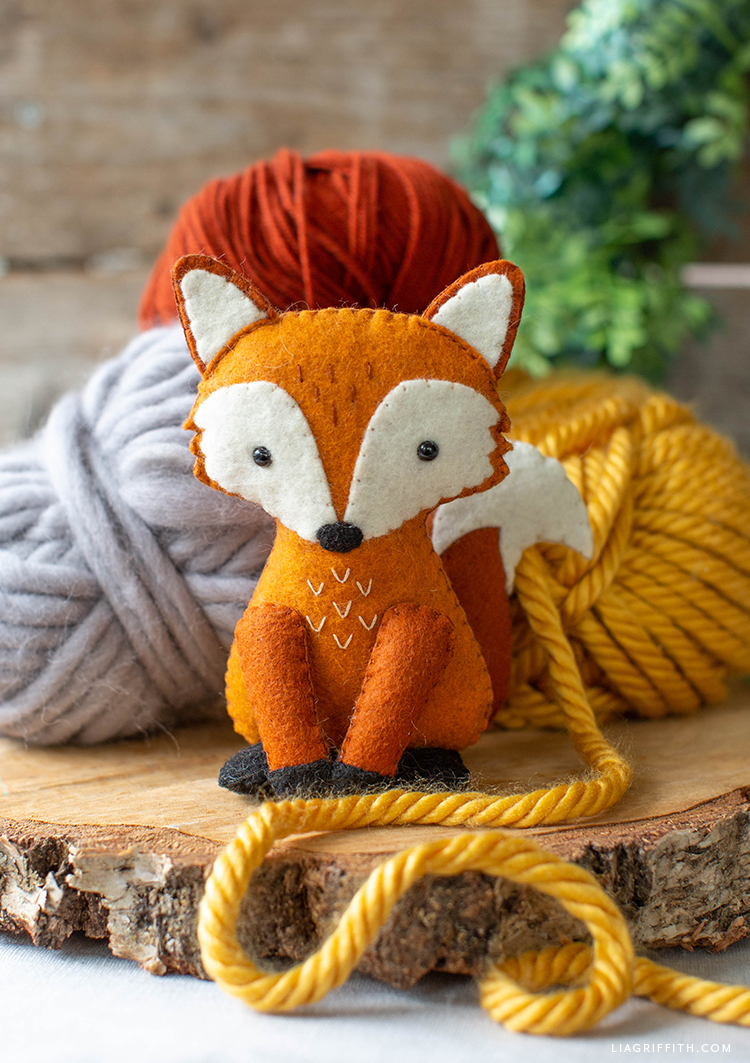 felt red fox stuffie with balls of yarn in grey, yellow, and reddish orange