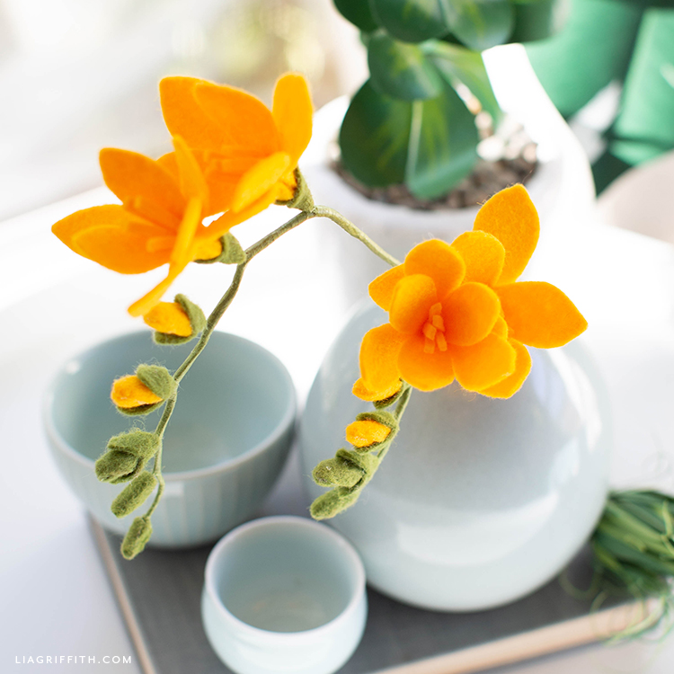 felt freesia flowers in white vase on tray with white bowls