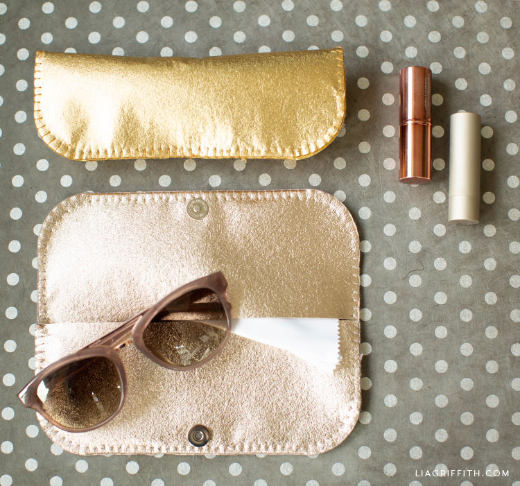 open metallic champagne felt glasses case with sunglasses and closed metallic gold felt glasses case next to lipstick on grey and white polka-dot background
