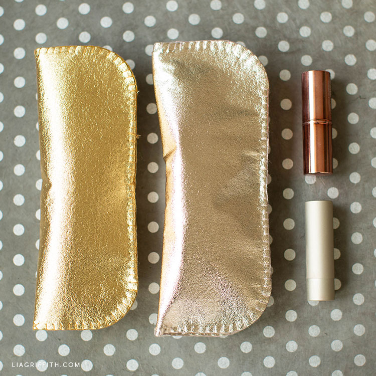 metallic gold and champagne felt eyeglass cases on grey and white polka-dot background next to lipstick