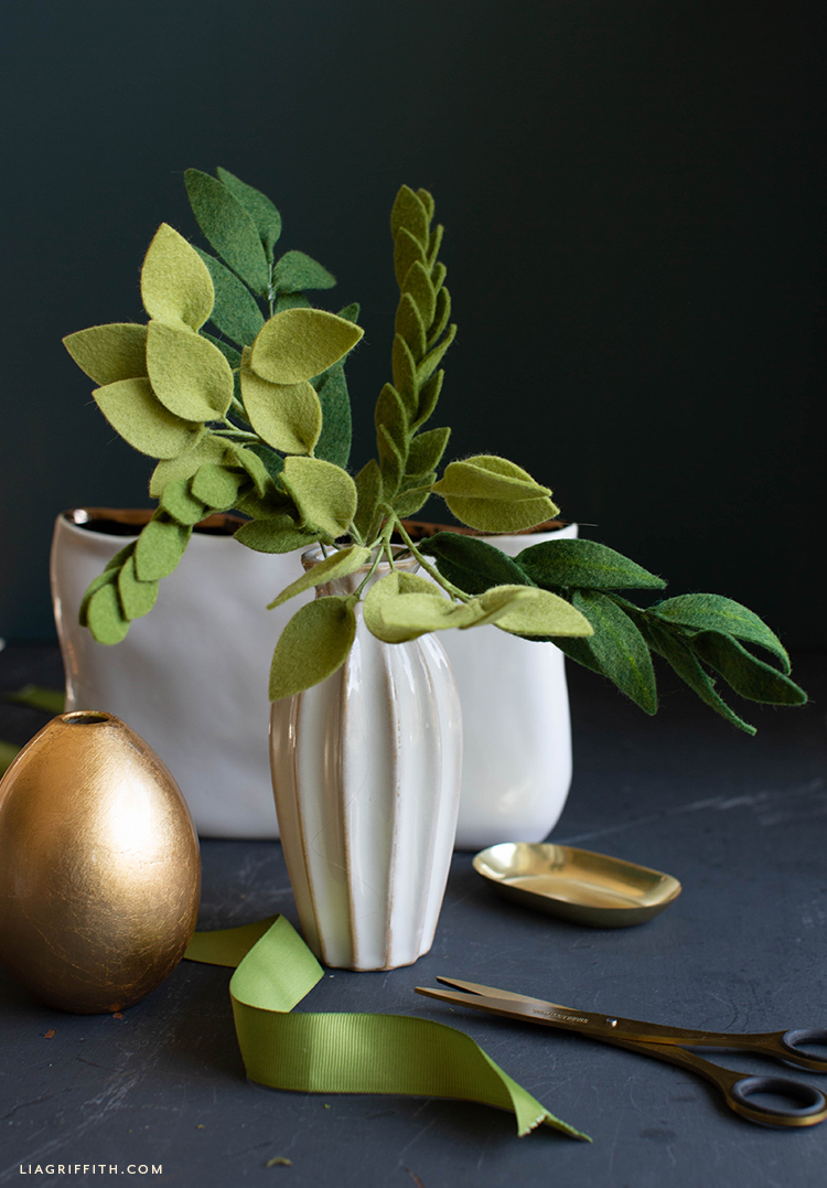 felt greenery stems in white vase next to empty gold vase and small gold tray
