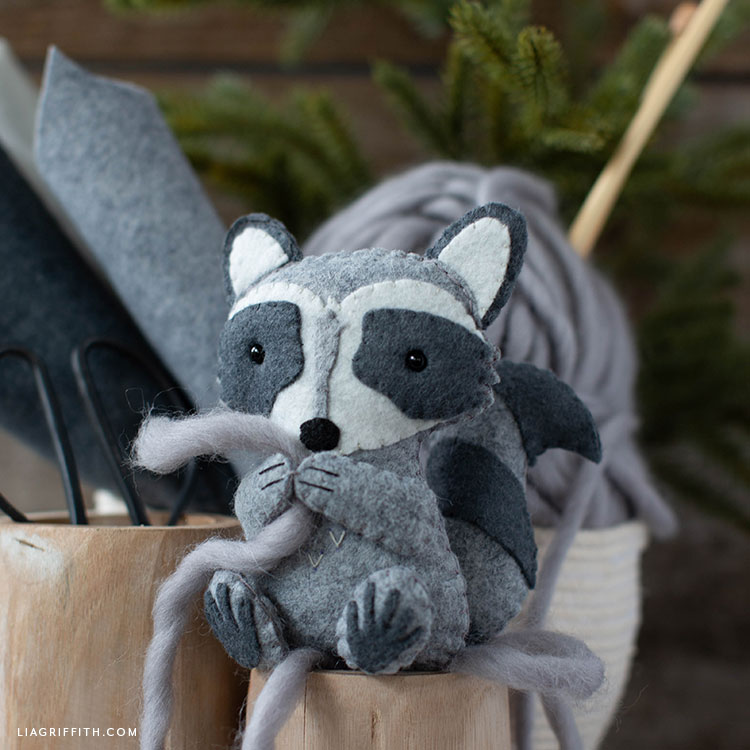 felt raccoon stuffie holding yarn