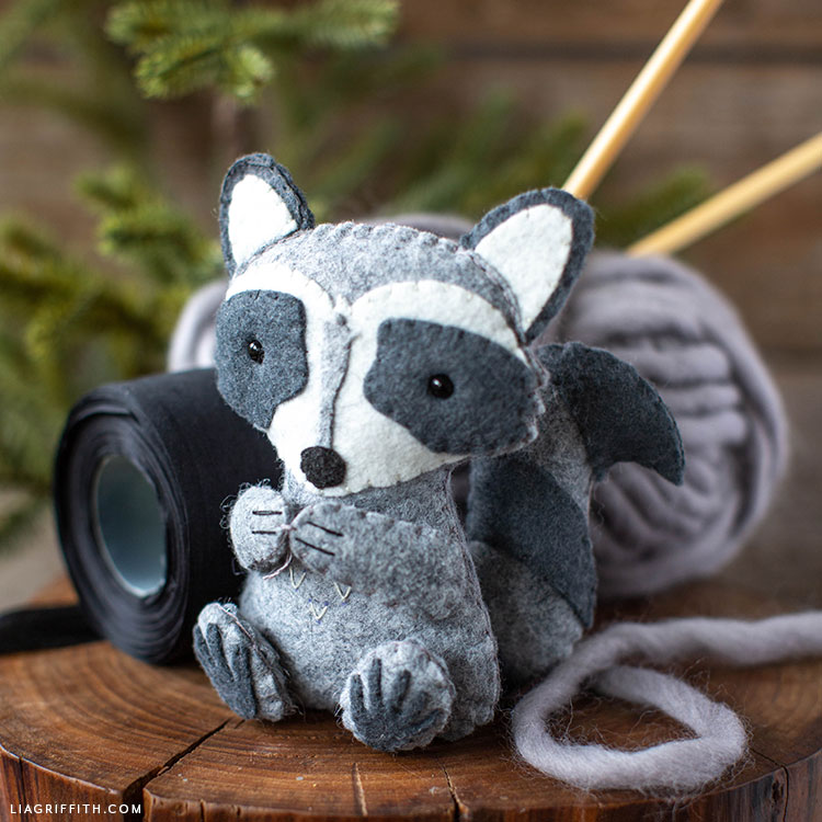 felt raccoon stuffie on stump with yarn and felt