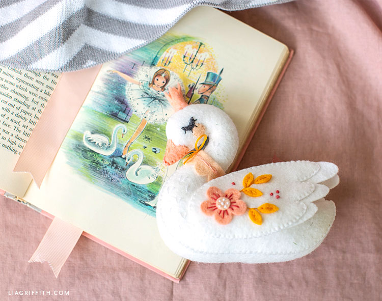 felt swan stuffie on the page of an open book against a pink sheet