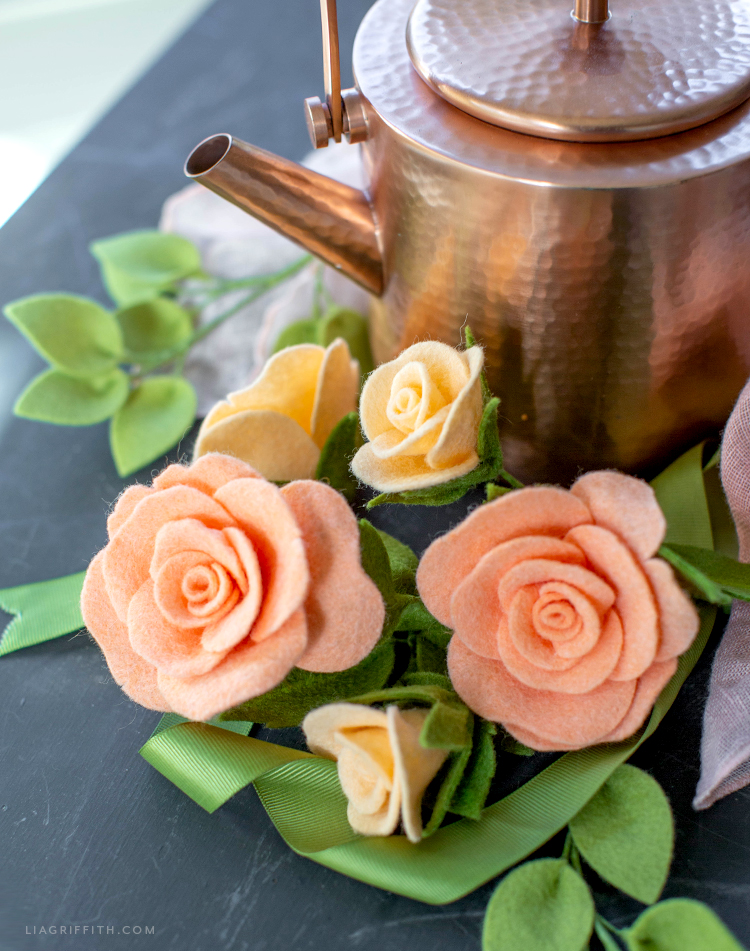 felt tea roses and buds next to copper teapot
