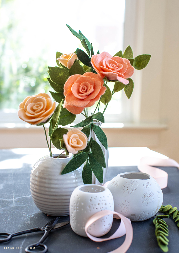 felt tea roses and buds in white vase in front of window