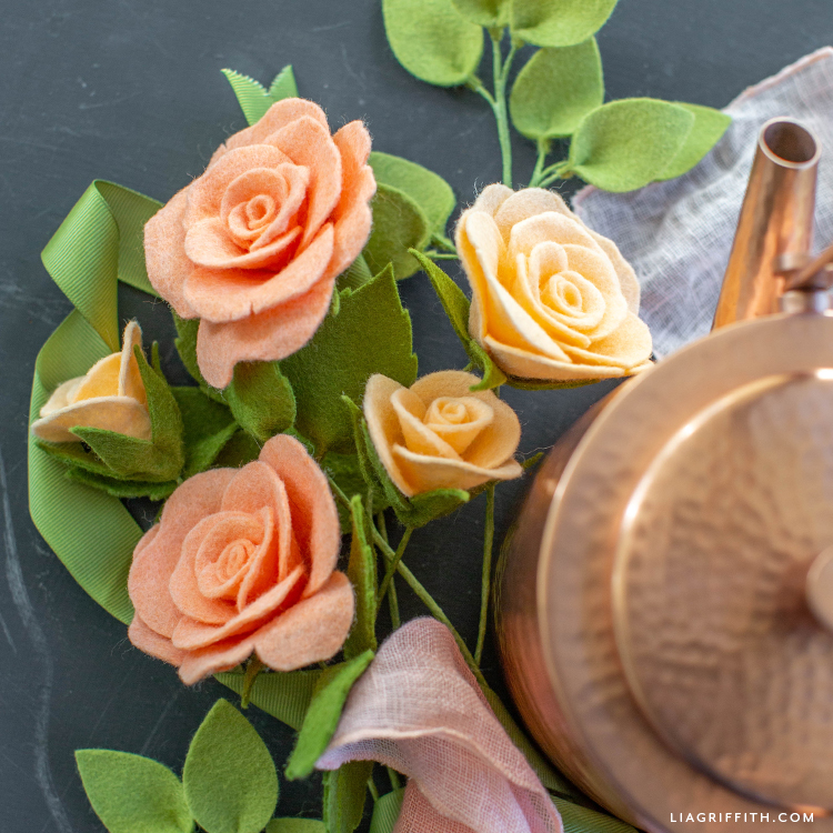 felt tea roses and buds with leaves next to copper teapot