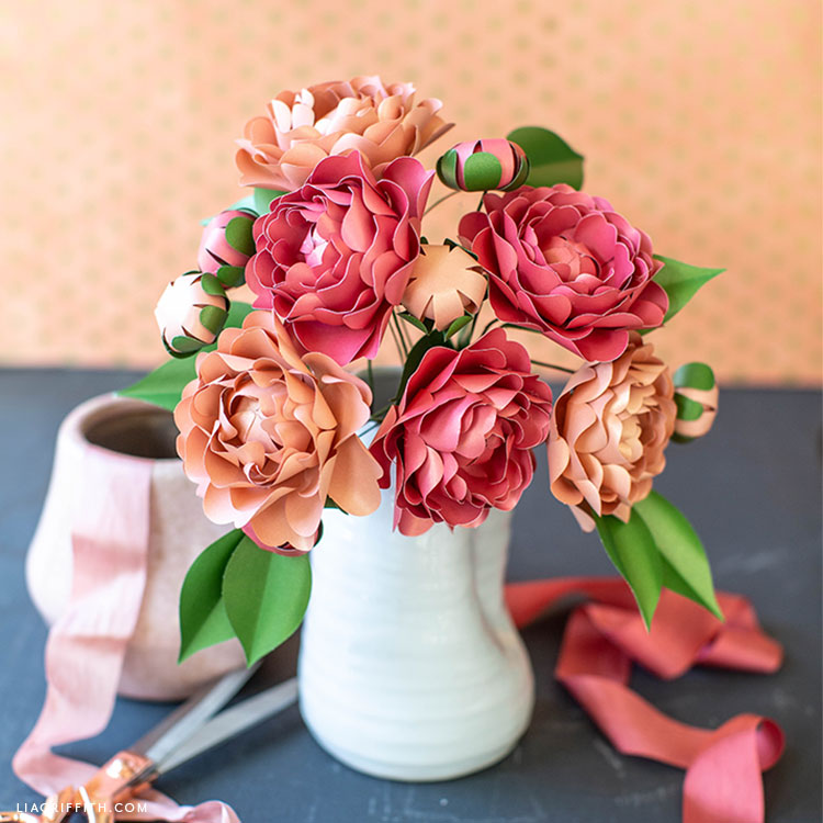 frosted paper camellia flowers in white vase next to pink ribbon