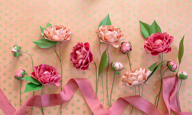 frosted paper camellia flowers with pink ribbon against orange and green polka-dot background