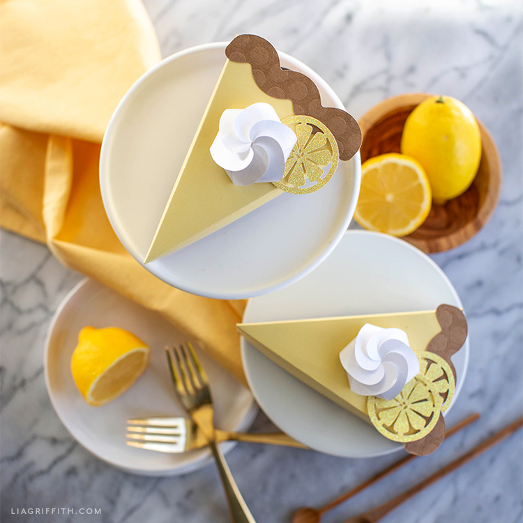 paper lemon tart pie boxes on plates next to yellow napkin, forks, and lemons