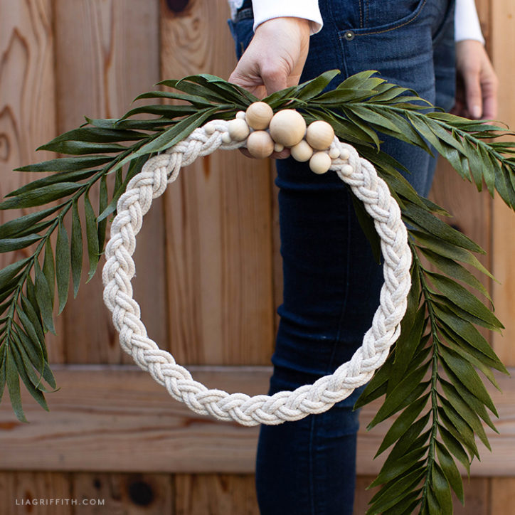 Woman holding braided rope wreath outside