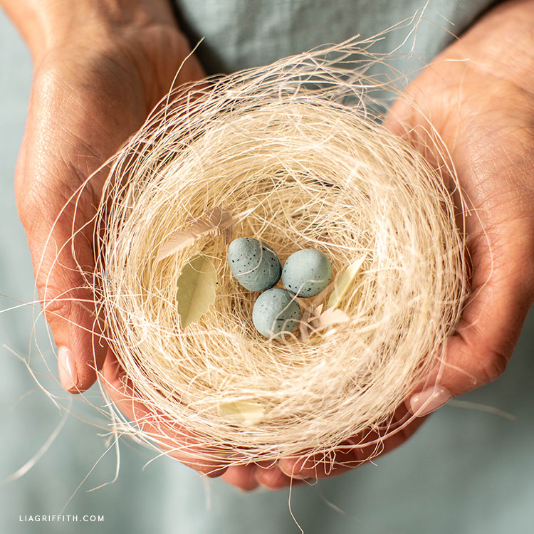 hands holding sisal robin's nest with spun cotton eggs