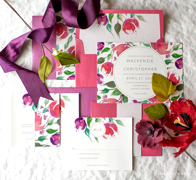 watercolor floral wedding invitations and envelopes next to paper flowers and purple ribbon