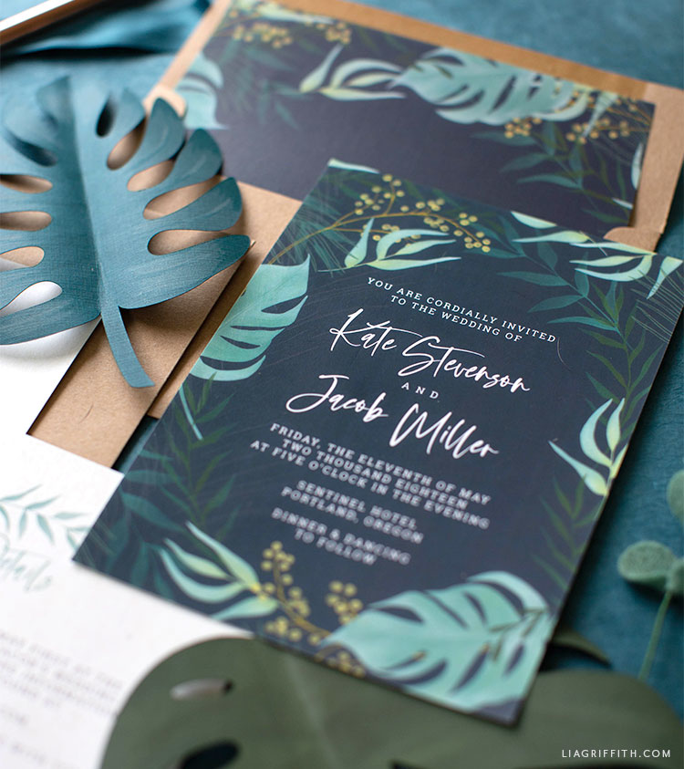 navy tropical wedding invitations with copper envelopes and paper monstera leaves