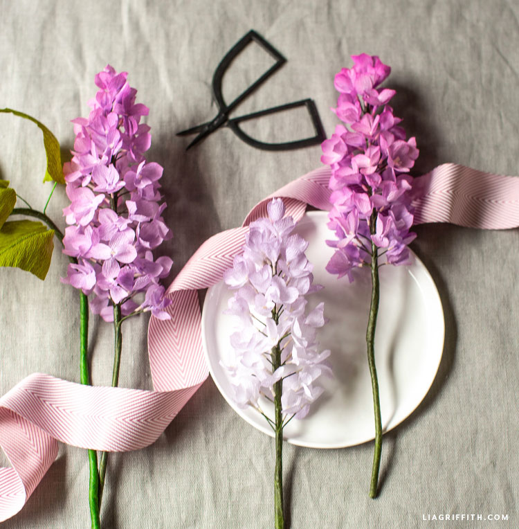 crepe paper lilac flowers with circular tray, ribbon, and scissors