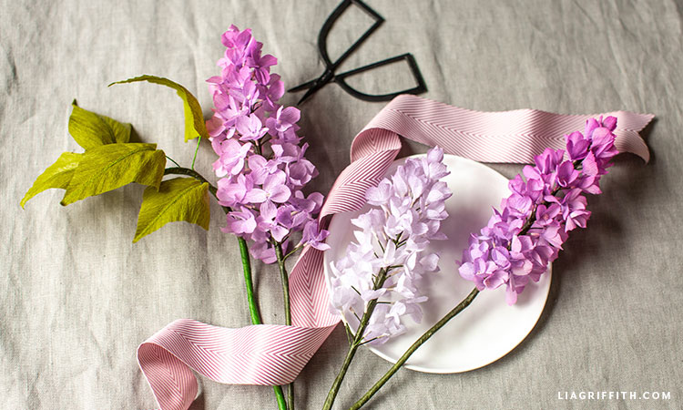 purple crepe paper lilac flowers styled with scissors, ribbon, and small dish