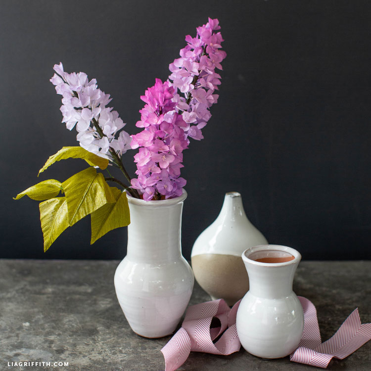 pink and purple crepe paper lilac flowers in white vase next to empty vases