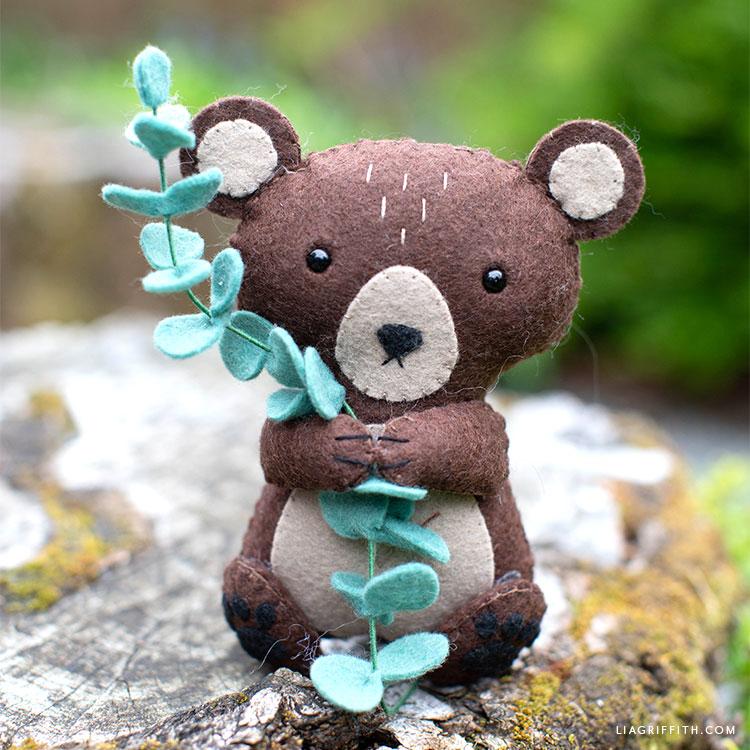 felt brown bear stuffie on tree stump outside holding a felt eucalyptus sprig