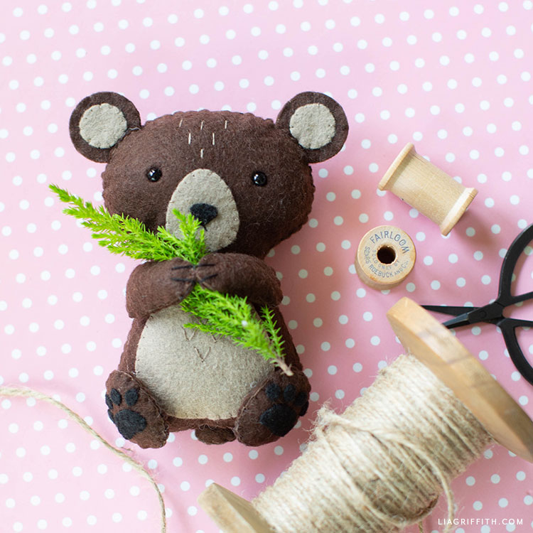 felt brown bear stuffie holding a small pine tree sprig next to spool of twine