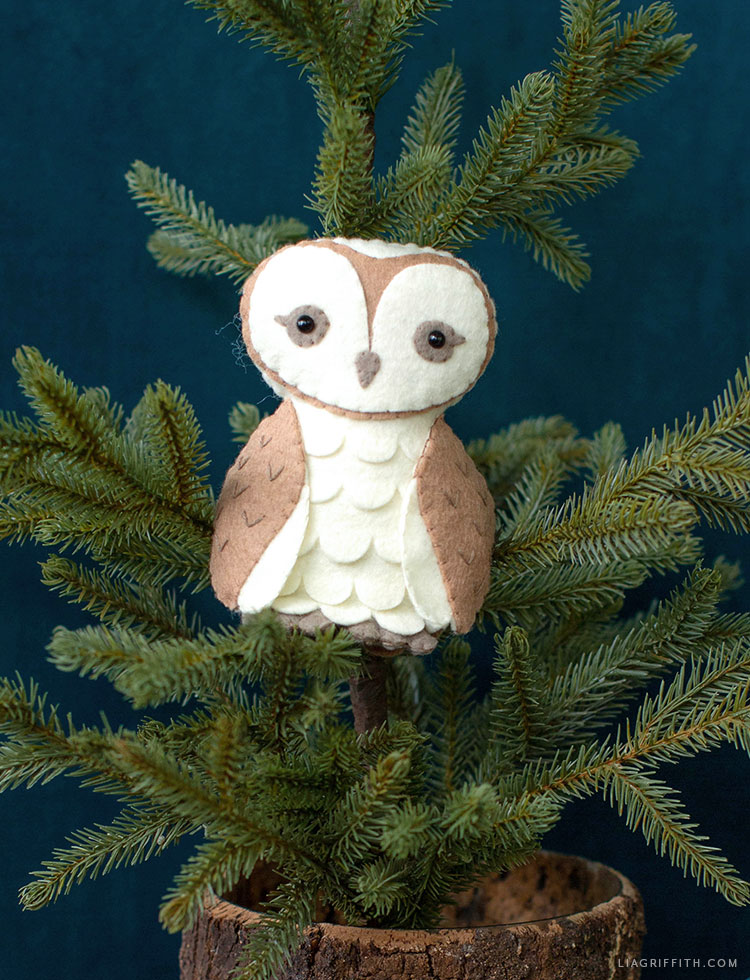 felt barn owl stuffie sitting in little pine tree