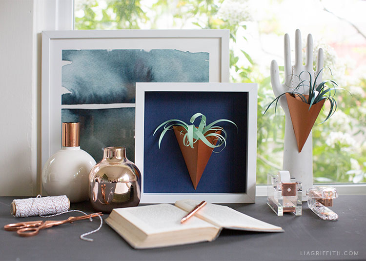 paper air plant vase in frame next to framed art, open book with pen, vases, and hand decor