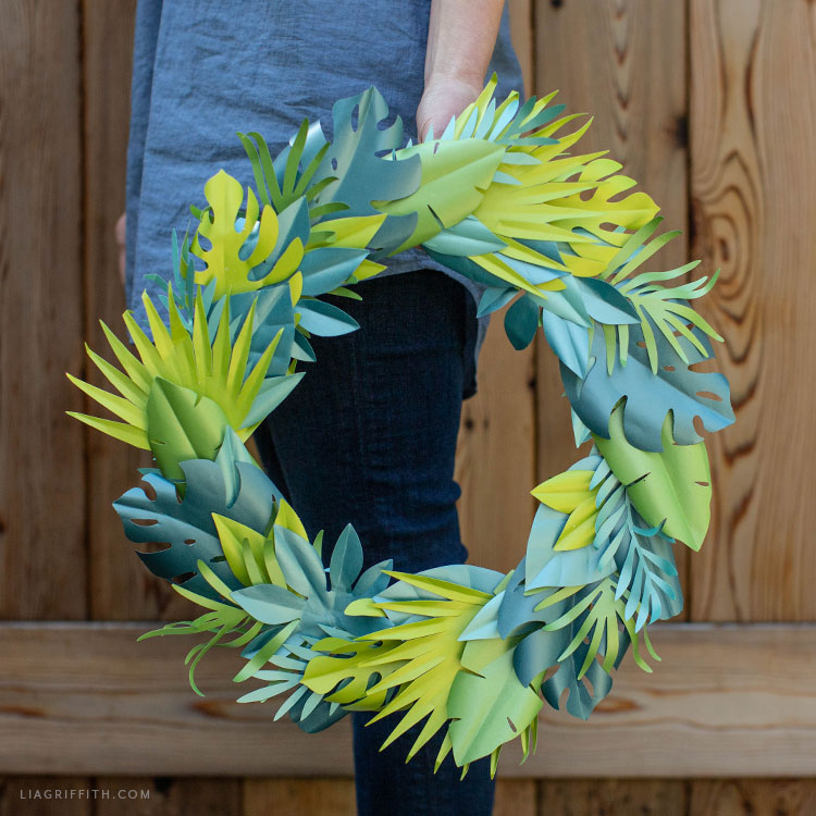 Person holding frosted paper tropical wreath outside by fence