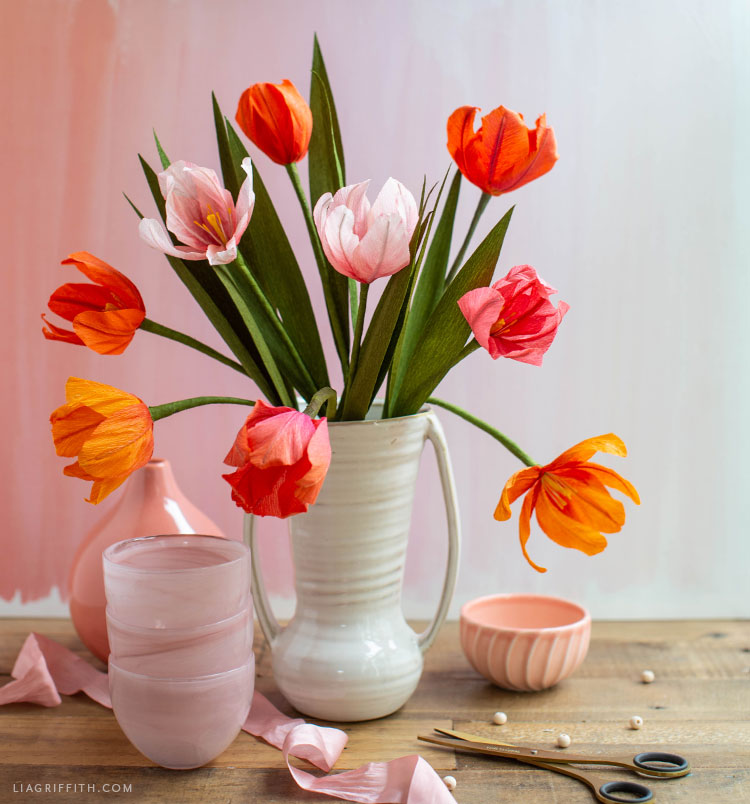 ombré crepe paper tulips in white vase next to pink vase and pink bowl