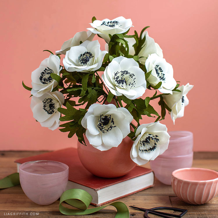 crepe paper anemone flowers in pink vase on pink book next to pink bowls