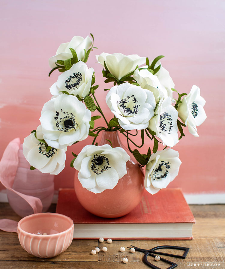 black and white crepe paper anemone flowers in pink vase on pink book with pink background