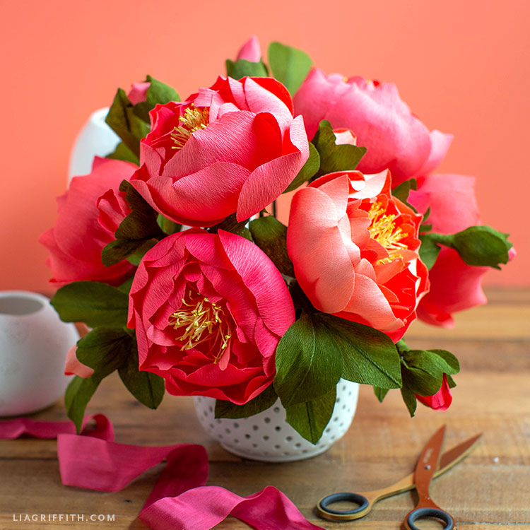 crepe paper peony flower arrangement in vase next to pink ribbon and scissors