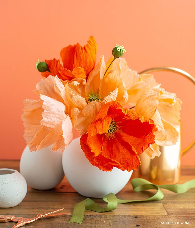 orange and peach crepe paper poppies in white vase