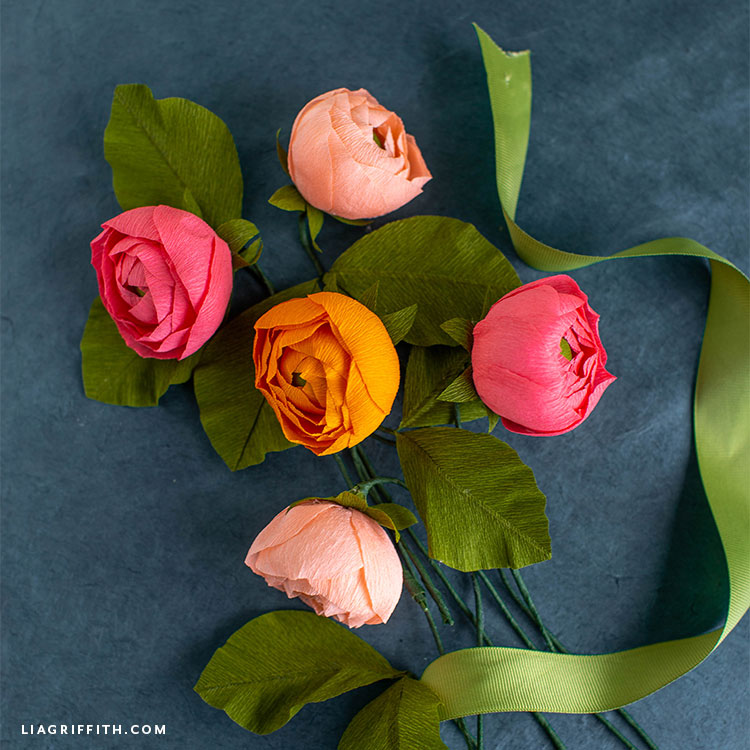 blush, pink, and orange crepe paper ranunculus flowers with leaves
