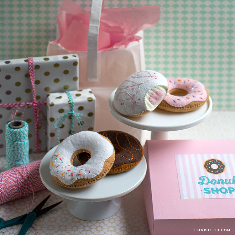 felt donuts on cake stand next to wrapped presents, donut shop box, and twine