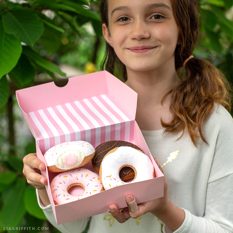 Girl holding donut box with felt donuts inside