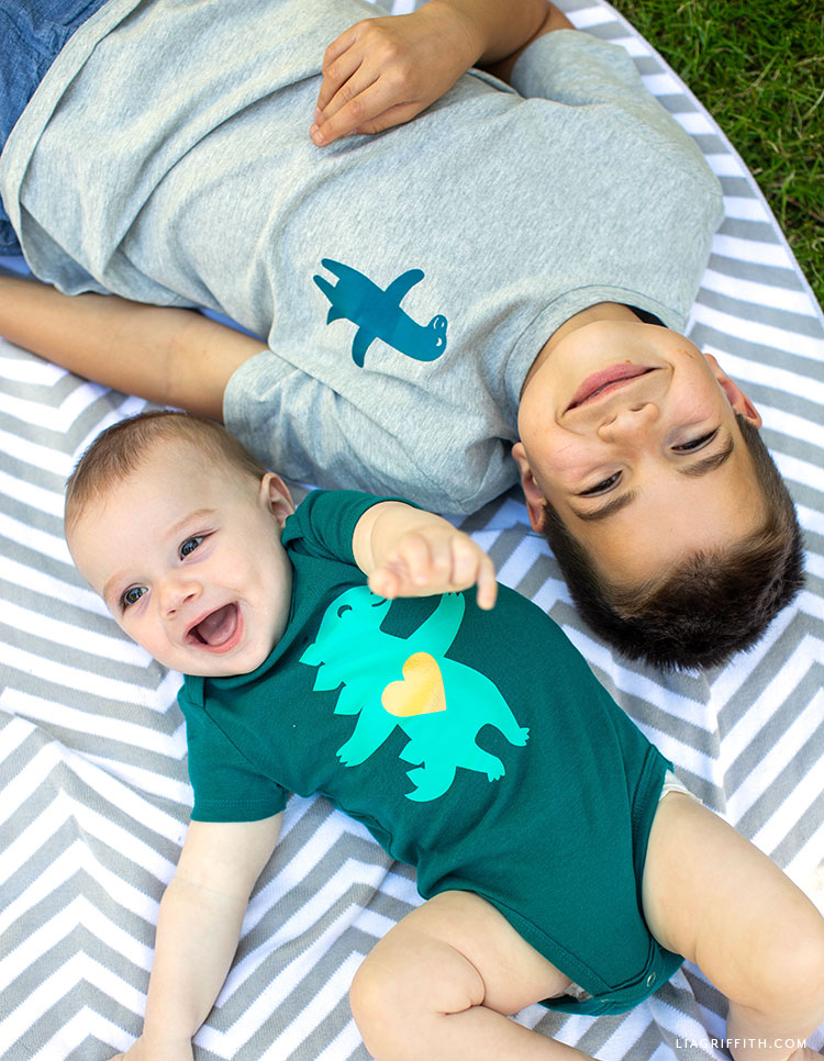 Baby wearing dinosaur onesie and boy wearing dinosaur t-shirt laying outside on the ground
