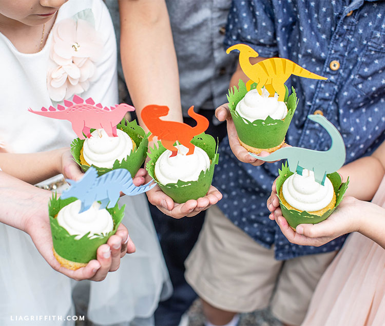 Kids holding cupcakes with dinosaur toppers